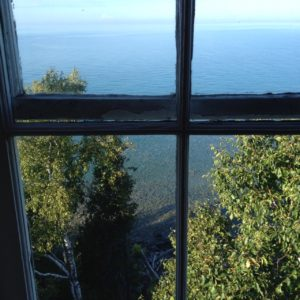view from old lighthouse on the Bruce Peninsula, looking out over the clear waters of Georgian Bay, framed by the old wood of the window frame
