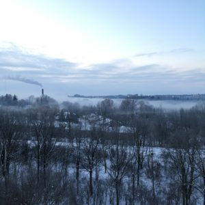 view from the window of a winter morning, smokestack streaming left, fog lifting up from the river, train tracks running horizontally through the middle foreground