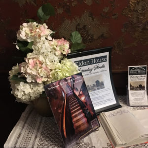 Resting on the table with the guestbook and vase of flowers in Eldon House is the digital art photograph of the stairs becoming the Himalayas with a QR code linking to the audio recording of the March 4 performance reading of The Dream Life of Teresa Harris, Augmented Reality at historic Eldon House exhibit.