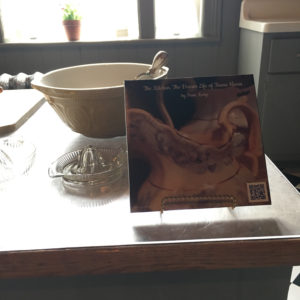 Kitchen table with bowl and juicer with window lit in background, Eldon House. On the table stands an image of a pitcher with QR code bottom R linking to the video footage of the March 4 performance reading of The Dream Life of Teresa Harris for the Augmented Reality at historic Eldon House exhibit.