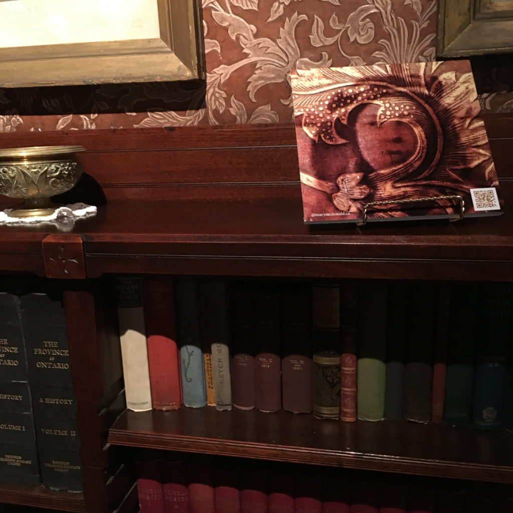 A bookshelf in the library at Eldon House, with an image of Teresa Harris superimposed by the curling leaf of the ornate wallpaper found in the room with QR code on the photo, linking to the animation for the Augmented Reality at historic Eldon House exhibit, Victorian in Nature